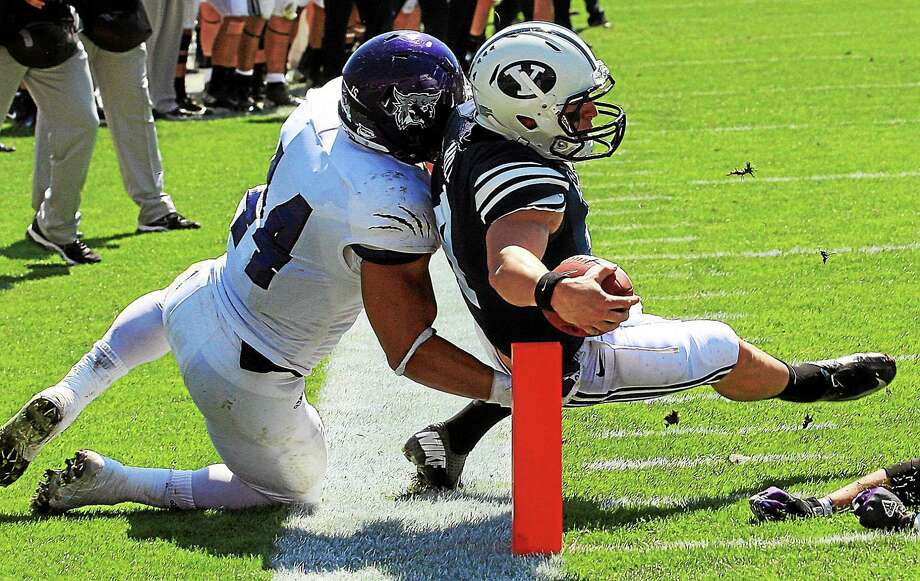 This Sept. 8, 2012 file photo shows Brigham Young quarterback Taysom Hill scoring as Weber State linebacker Anthony Morales goes for the tackle. Photo: Rick Bowmer — The Associated Press  / AP