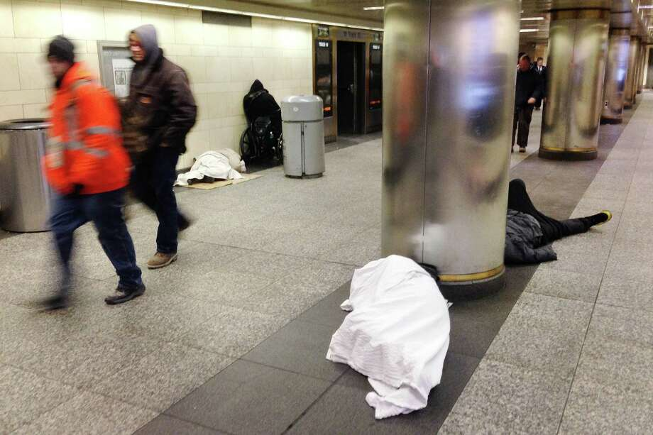 Homeless people, seeking shelter from the cold, sleep on the floor of New York's Penn Station as commuters walk past, Thursday, Jan. 8, 2015. Temperatures were expected to drop to 7, (-14 C) in New York City, Thursday. Many cities experiencing cold weather have opened warming stations for residents lacking heat. But extra care is being taken to protect the homeless. (AP Photo/Mark Lennihan) Photo: AP / AP