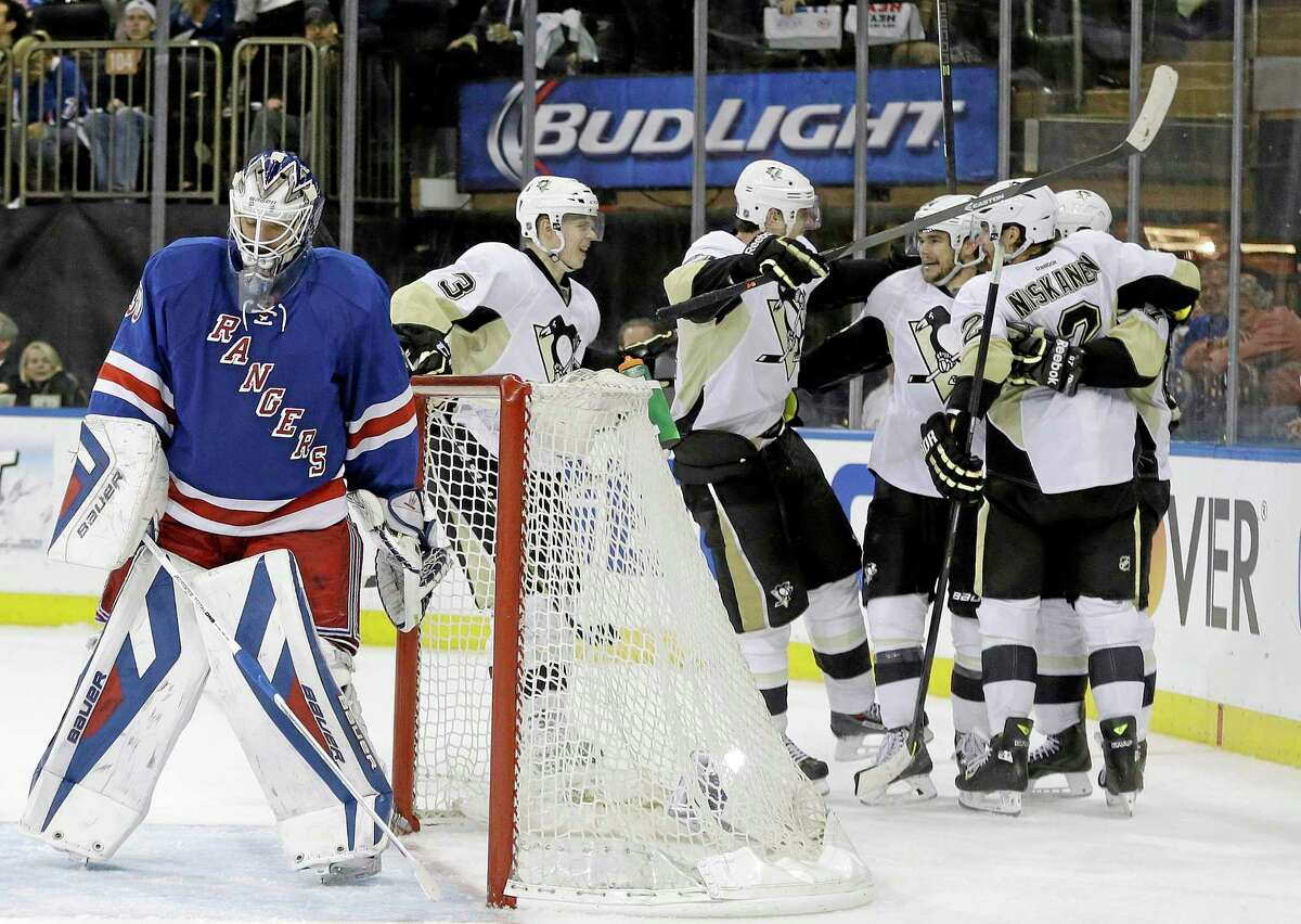 New York Rangers goalie Henrik Lundqvist reacts as the Pittsburgh Penguins celebrate a goal by Chris Kunitz during the third period of Wednesday's game in New York.