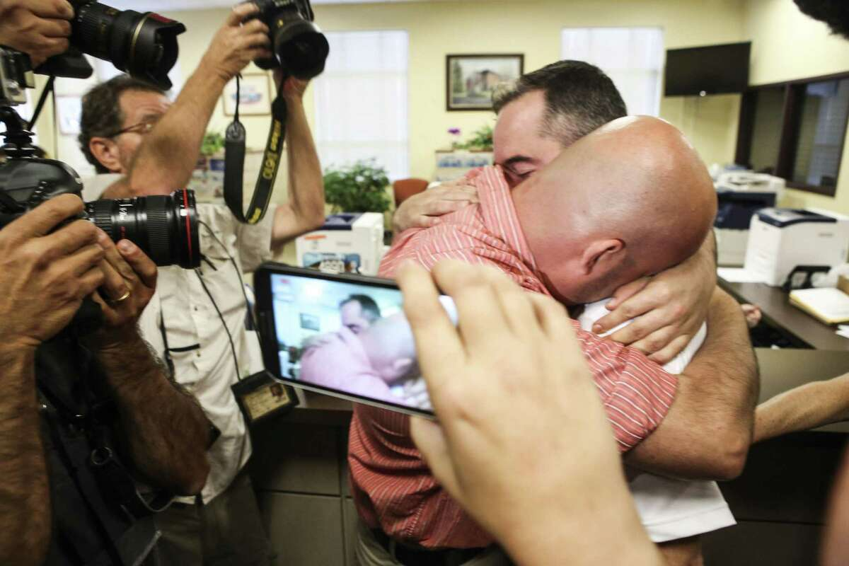 James Yates, right, hugs his partner William Smith Jr., after receiving their marriage license at the Rowan County Judicial Center in Morehead, Ky., Friday, Sept. 4, 2015. Deputy clerk Brian Mason issued the license, congratulating the couple and shaking their hands as he smiled.