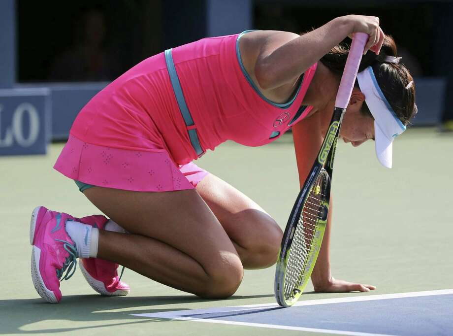 Peng Shuai drops to her knees in pain during the semifinals of the U.S. Open against Caroline Wozniacki on Friday in New York. Peng left the court in a wheelchair and retired from the game, forfeiting it to Wozniacki. Photo: Mike Groll — The Associated Press  / AP