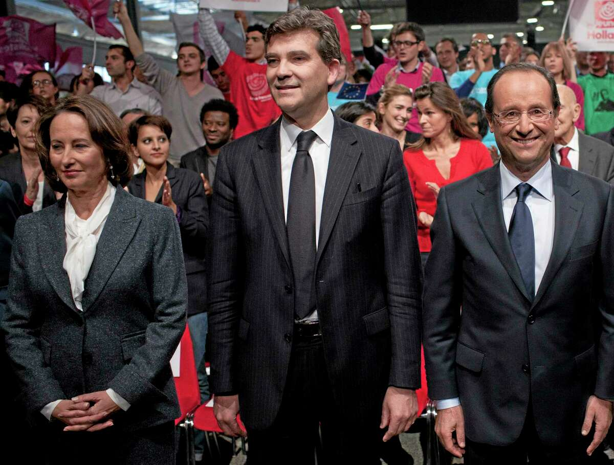 FILE - In this Oct.22, 2011 file photo, then French Socialist Party candidate for the 2012 presidential elections Francois Hollande, right, attends a nomination ceremony, in Paris. French actress Julie Gayet appears smiling in background, between Hollande and Arnaud Montebourg, center. Hollande's first lady, journalist Valerie Trierweiler was hospitalized last Friday after a tabloid-style magazine reported that he is secretly having an affair with French movie actress Gayet, and published photos it said proved the liaison. At left is Hollande's former companion Segolene Royal. At left is former Hollande's companion Segolene Royal. (AP Photo/Thibault Camus, File)