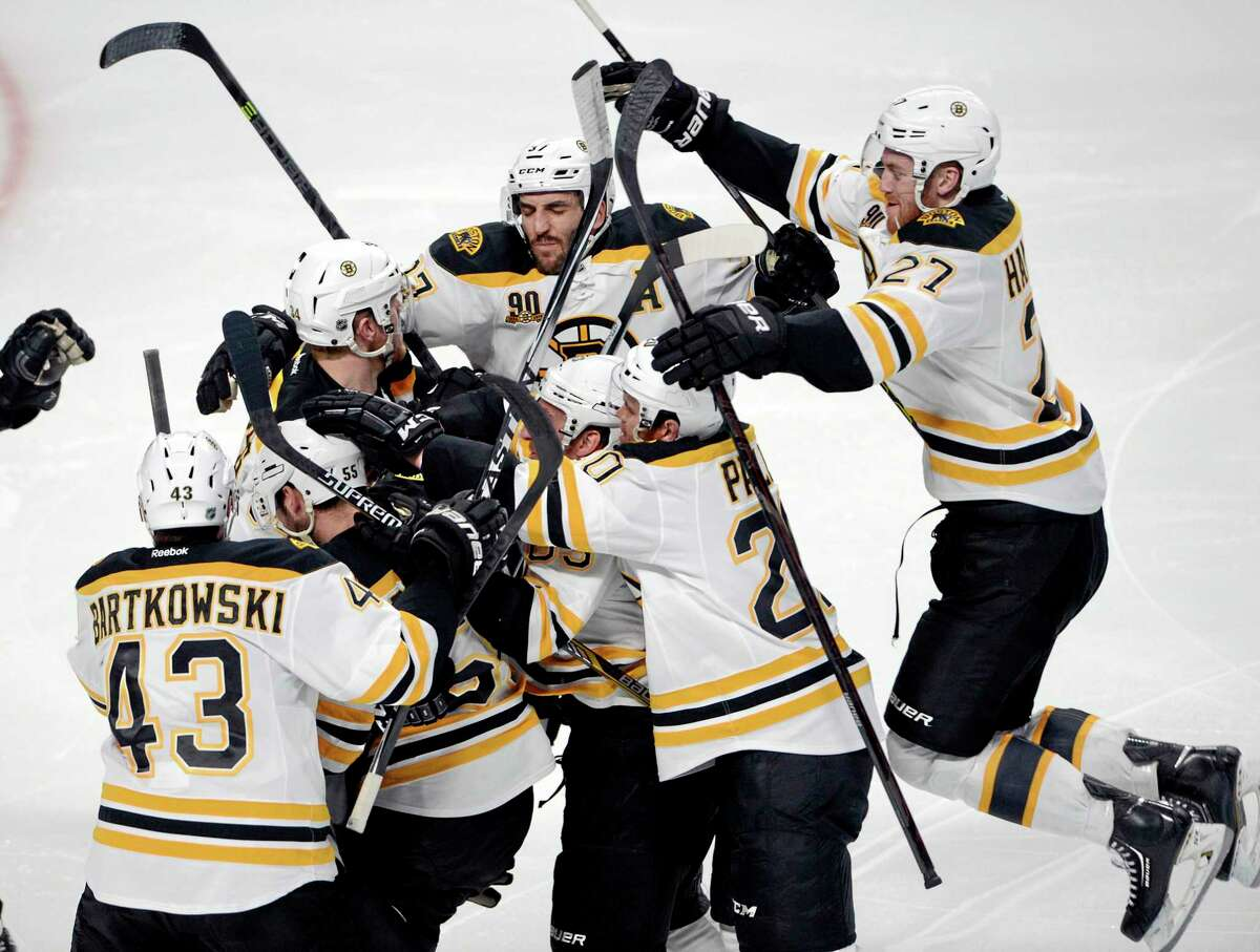 The Bruins' Matt Fraser is mobbed by teammates after scoring the game-winning goal against the Montreal Canadiens during the first overtime period in Game 4 in the second round of the NHL Stanley Cup playoffs Thursday.