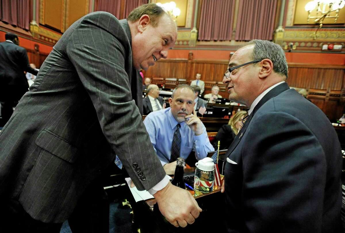 Connecticut State Rep. Stephen Dargan, D-West Haven, left, and House Minority Leader Larry Cafero, R-Nowalk, right, speak to one another as House Majority Leader Joseph Aresimowicz, D-Berlin, center, looks on at the Capitol on the final day of session, Wednesday, May 7, 2014, in Hartford, Conn. (AP Photo/Jessica Hill)