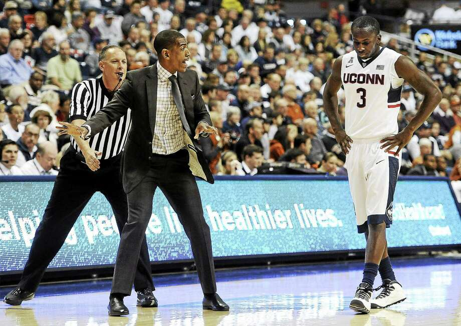 UConn coach Kevin Ollie, left, talks with Terrence Samuel during a game last season. Photo: The Associated Press File Photo  / FR125654 AP