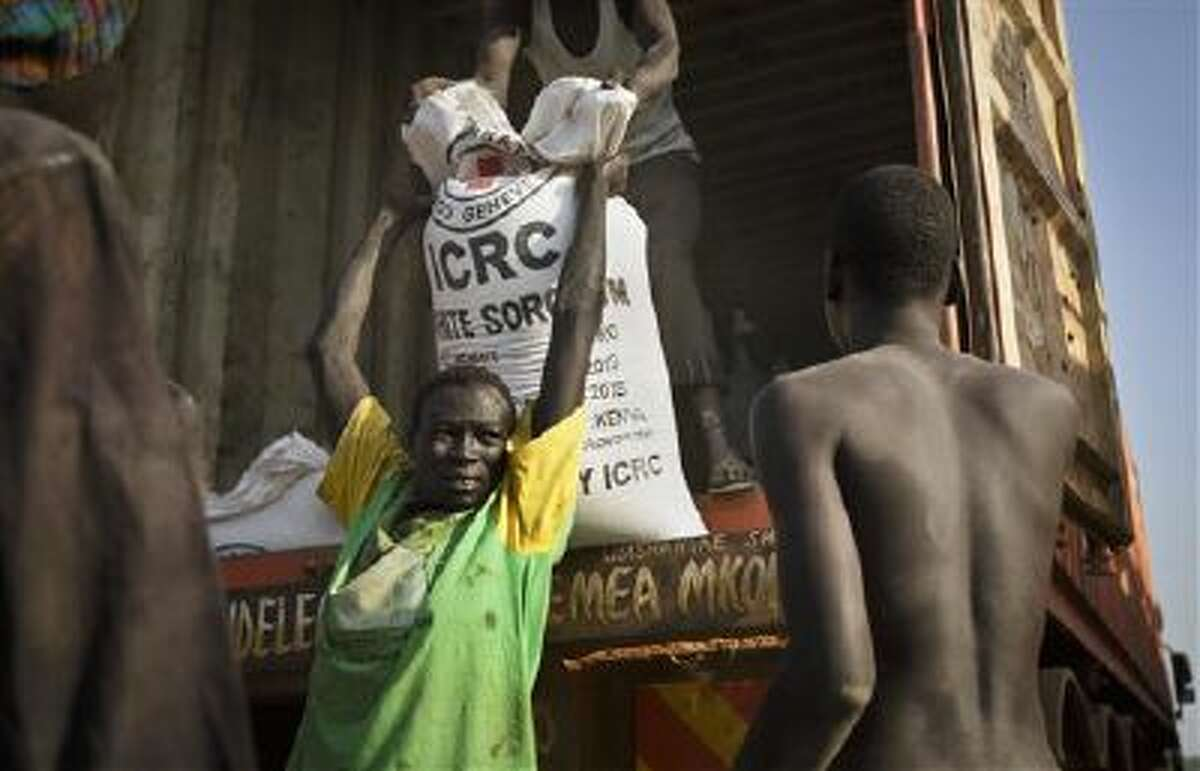 A man unloads food assistance supplied by the international Red Cross that arrived by boat and then truck in the town of Awerial, South Sudan.