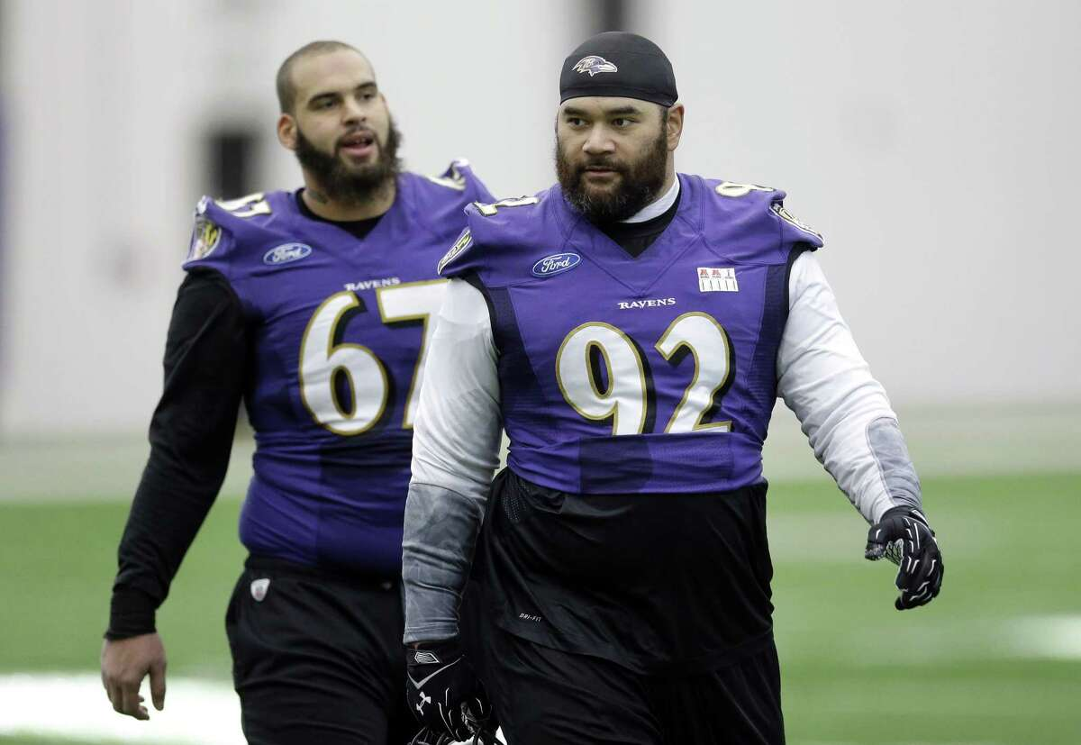 Baltimore Ravens defensive end Haloti Ngata (92) walks off the field in front of teammate Lawrence Guy after practice Wednesday in Owings Mills, Md.