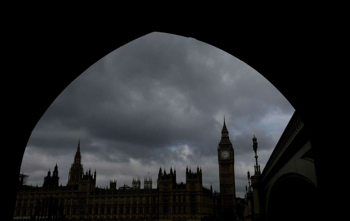 Britain's Houses of Parliament are silhouetted through an archway in London, Thursday, May 7, 2015. Britain's most unpredictable general election in decades gets under way Thursday with polls showing the two biggest parties Labour and the Conservatives running in a virtual dead heat. The election could decide issues such as whether Britain will remain a member of the European Union, whether it will close its doors to immigrants and whether it will continue with austerity programs.