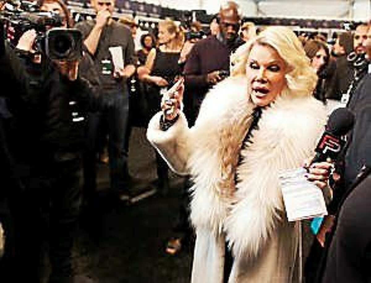 """In this Feb. 14, 2012, file photo, Joan Rivers tours backstage with her camera crew for E!'s """"Fashion Police,"""" before the Badgley Mischka show during Fashion Week in New York."""