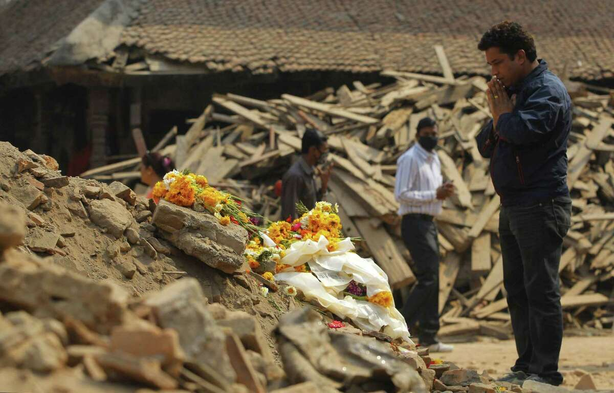 A Nepalese man offers prayers in front of floral tributes placed in memory of victims killed in last week's earthquake, at Basantapur Durbar Square in Kathmandu, Nepal, Thursday, May 7, 2015. The April 25 earthquake killed thousands and injured many more as it flattened mountain villages and destroyed buildings and archaeological sites in Kathmandu.