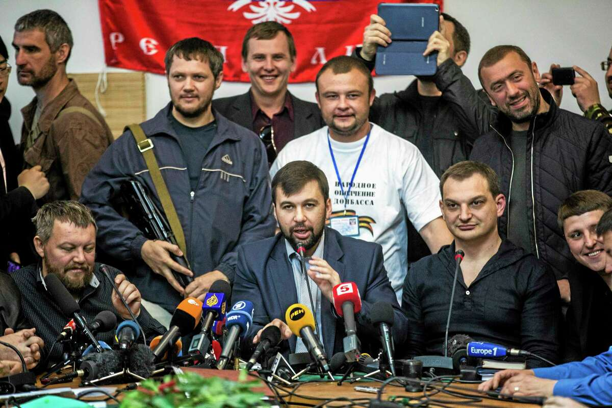 The head of the elections commission of the so-called Donetsk People's Republic, Denis Pushilin, center foreground, is seen during a press conference to inform the media about the referendum at the occupied administration building in Donetsk , Ukraine, Thursday, May 8, 2014. Today, the pro-Russia insurgency in eastern Ukraine decided Thursday to go ahead with Sunday's referendum on autonomy despite a call from Russian President Vladimir Putin to delay it. (AP Photo/Manu Brabo)