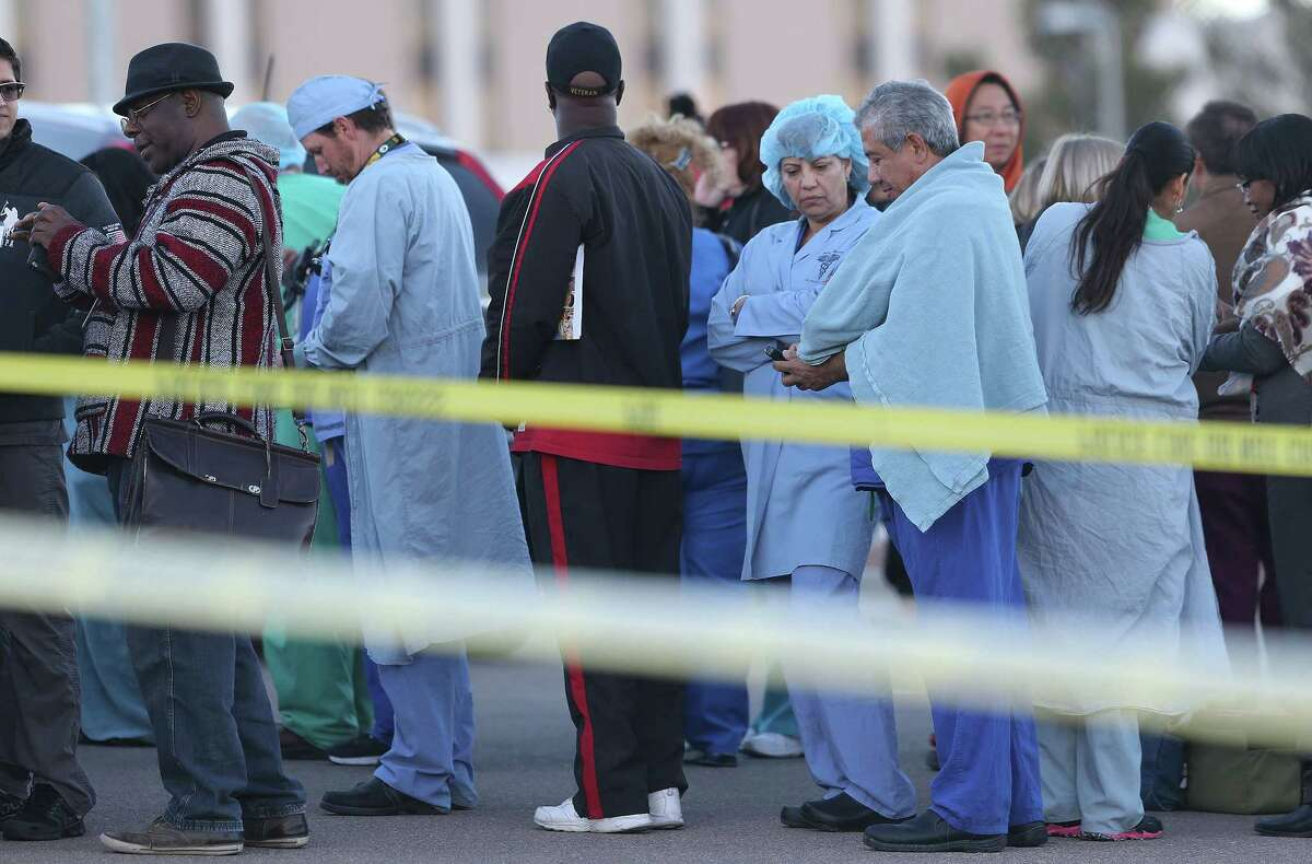 CORRECTS YEAR - Medical personnel waited with other VA and Beaumont Army Medical Center visitors in a parking lot outside the VA following a shooting inside the facility Tuesday, Jan. 6, 2015. A gunman opened fire at the veterans' medical clinic in West Texas on Tuesday, killing one other person, officials said. The gunman was also killed. (AP Photo/The El Paso Times, Victor Calzada)