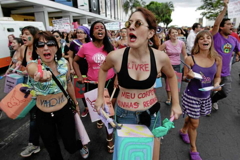 "A demonstrator with her body painted in Portuguese words ""Free. My body. My rules"" screams as she beats a drum and another holds up a stick of lipstick during a protest against sexism and in defense of women's rights in Brazil in this 2013 file photo. Photo: AP File Photo  / AP"
