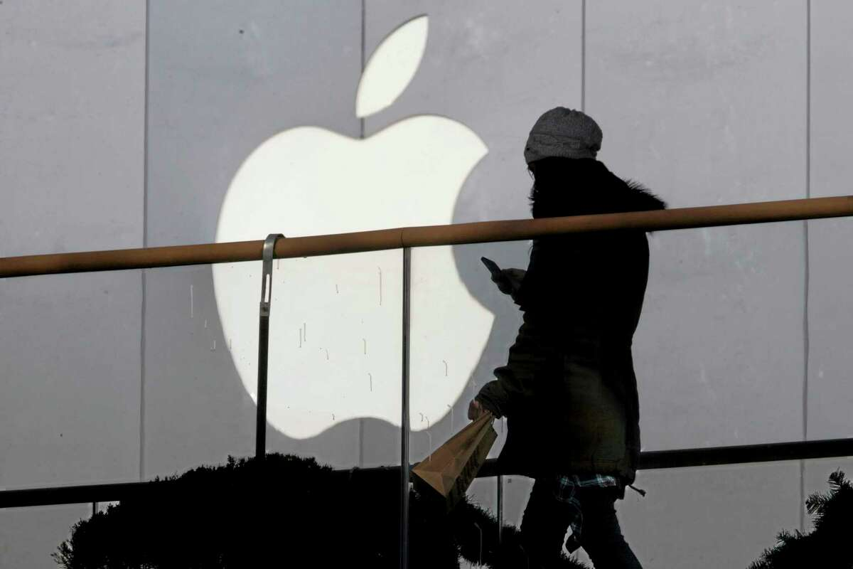 FILE - In this Dec. 23, 2013 file photo, a woman using a phone walks past Apple's logo near its retail outlet in Beijing. (AP Photo/Ng Han Guan, File)