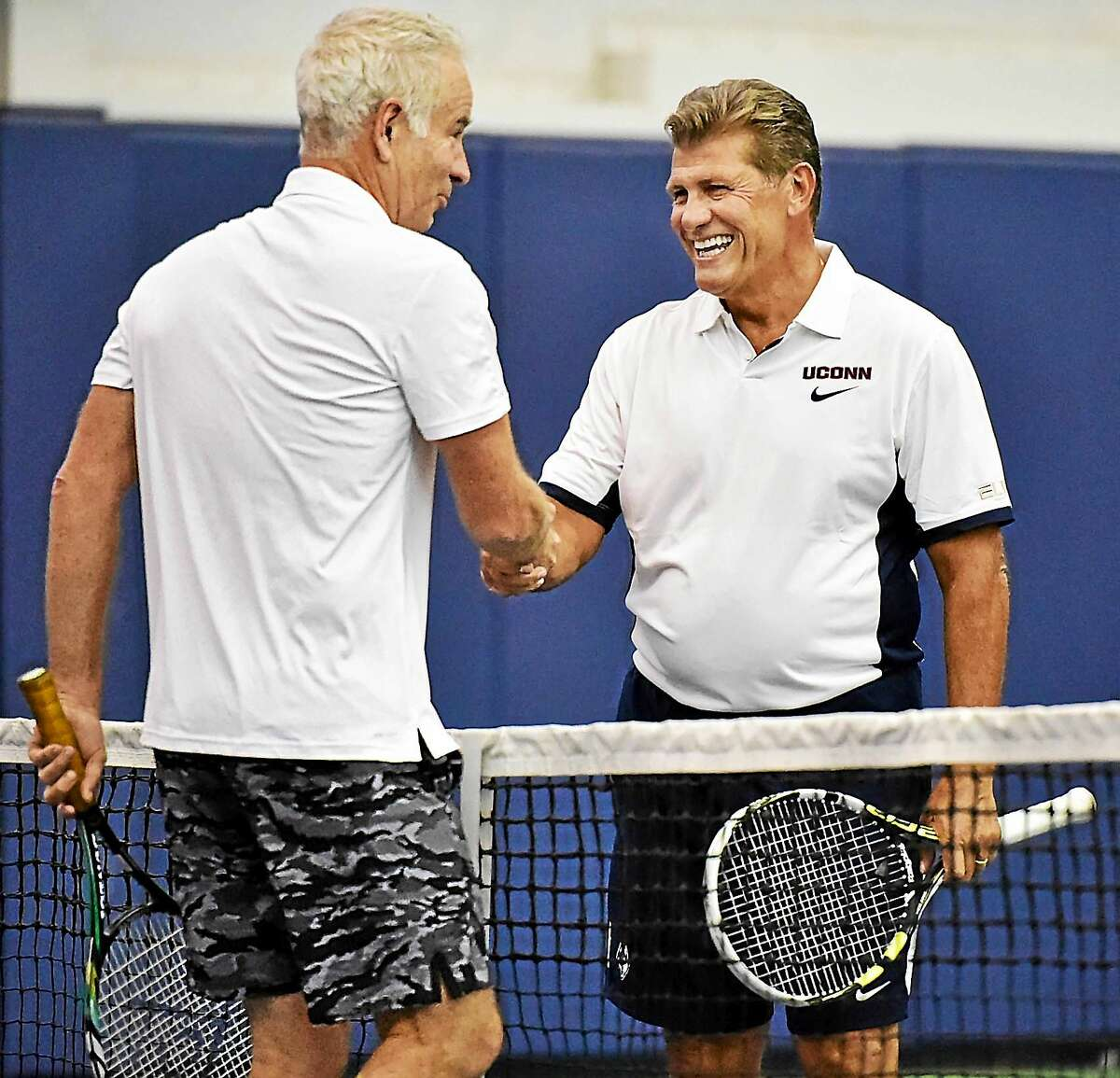 UConn women's basketball coach Geno Auriemma greets John McEnroe at the net following their match at the Cullman-Heyman Tennis Center at the Connecticut Open on Friday in New Haven.