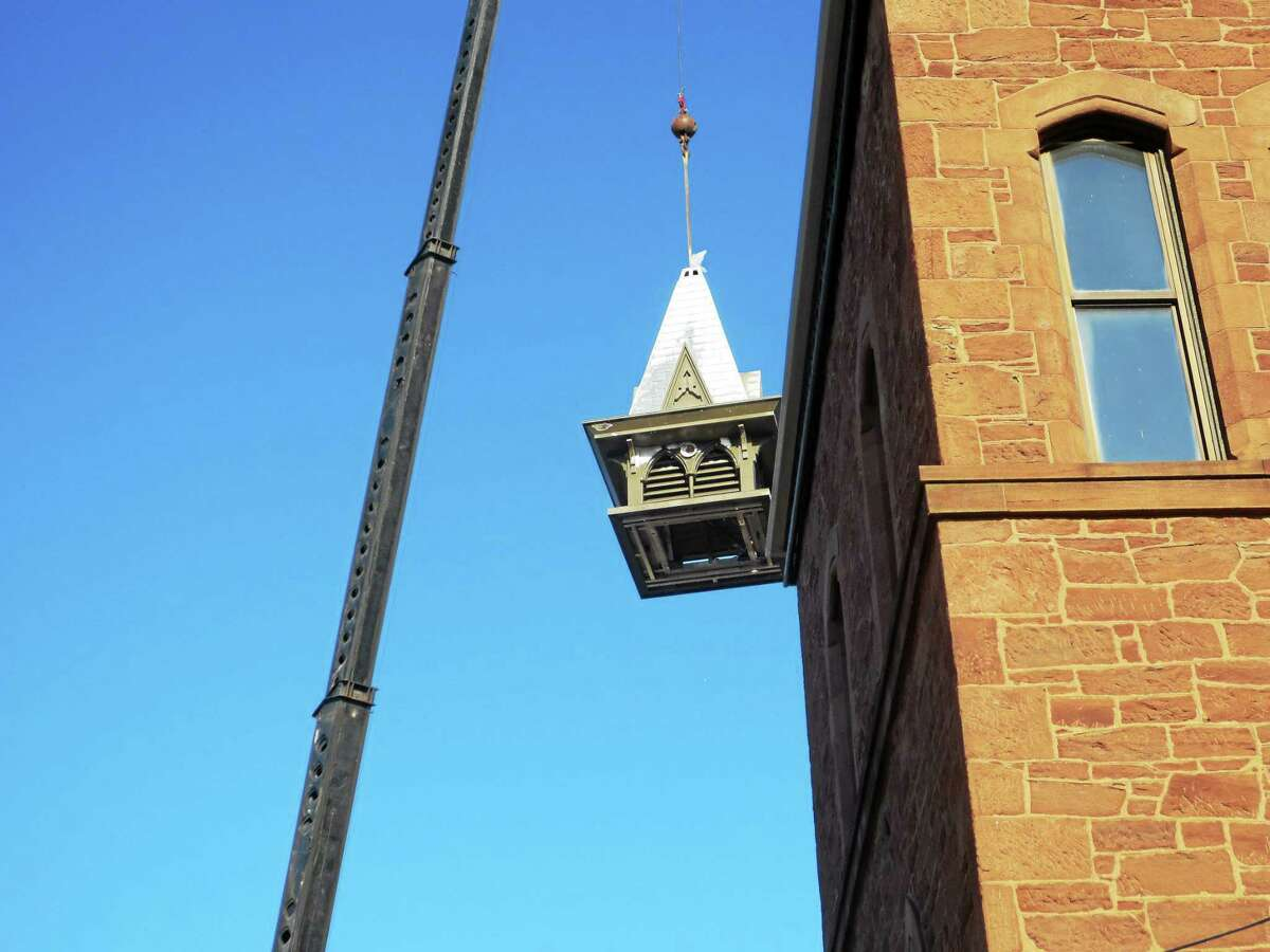 """A Marino Crane operator hoists a regal cupola atop the Russell Library on Broad Street in Middletown — capping off the three-quarter-of-a-million-dollar renovation project that will insure the facility offers residents a """"bridge to the future."""""""