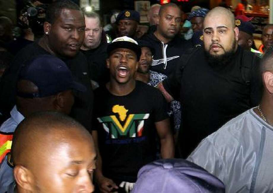 Boxer Floyd Mayweather Jr, center, on his arrival in Johannesburg Wednesday. Mayweather is doing a tour through the country.