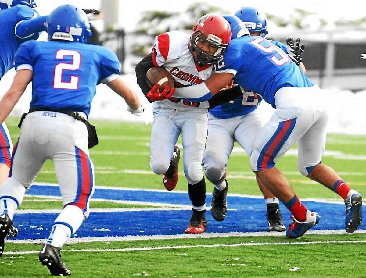 A Cromwell running back battles through Coginchaug defenders during last year's Thanksgiving Day matchup. Cromwell and Portland players, now playing as a combined team, are being investigated for possible locker room hazing.
