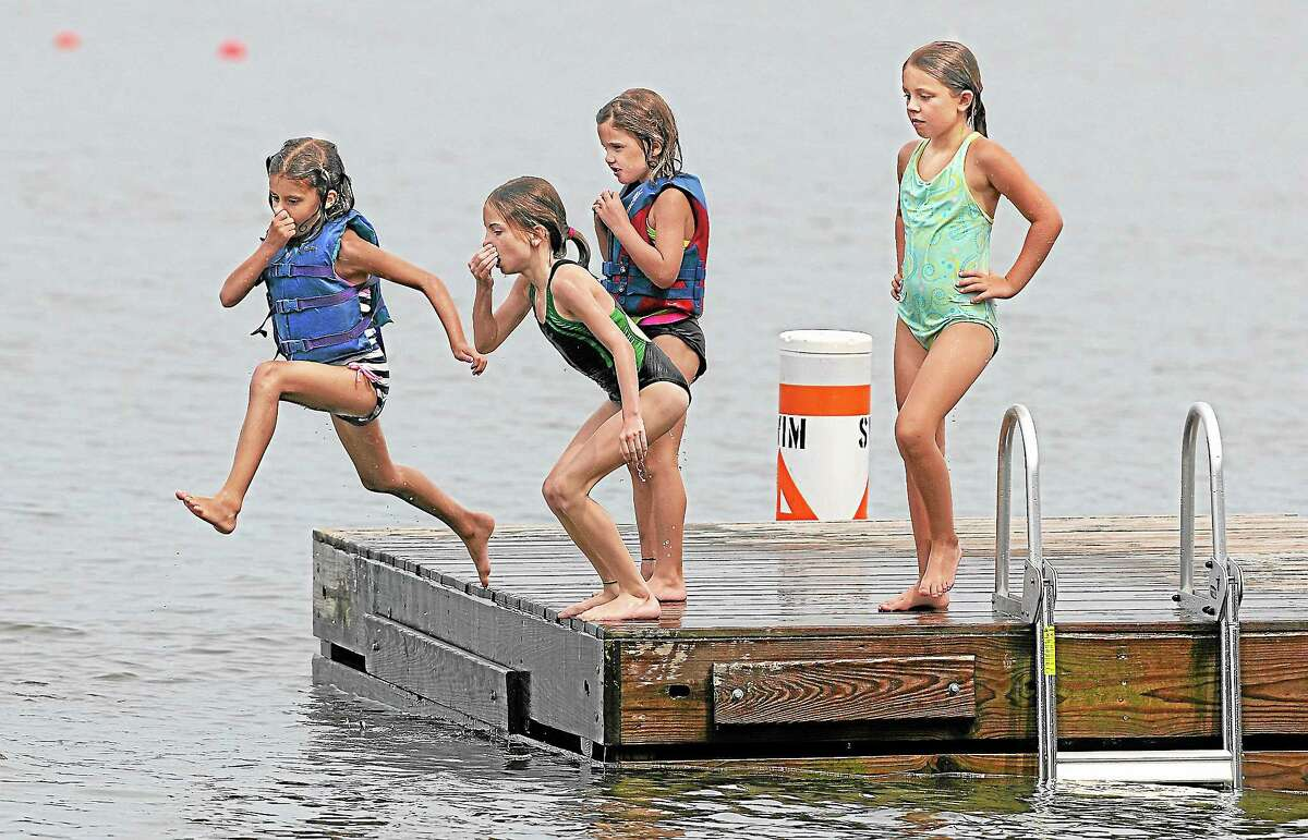 Grace Papa, 6, of Manchester, Lea Theophilos, 9, and her little sister Anna Theophilos, 6, of South Boston, and Brianne, 8 of East Hampton jump off the dock at Sears Park at Lake Pocotopaug in East Hampton in this file photo.