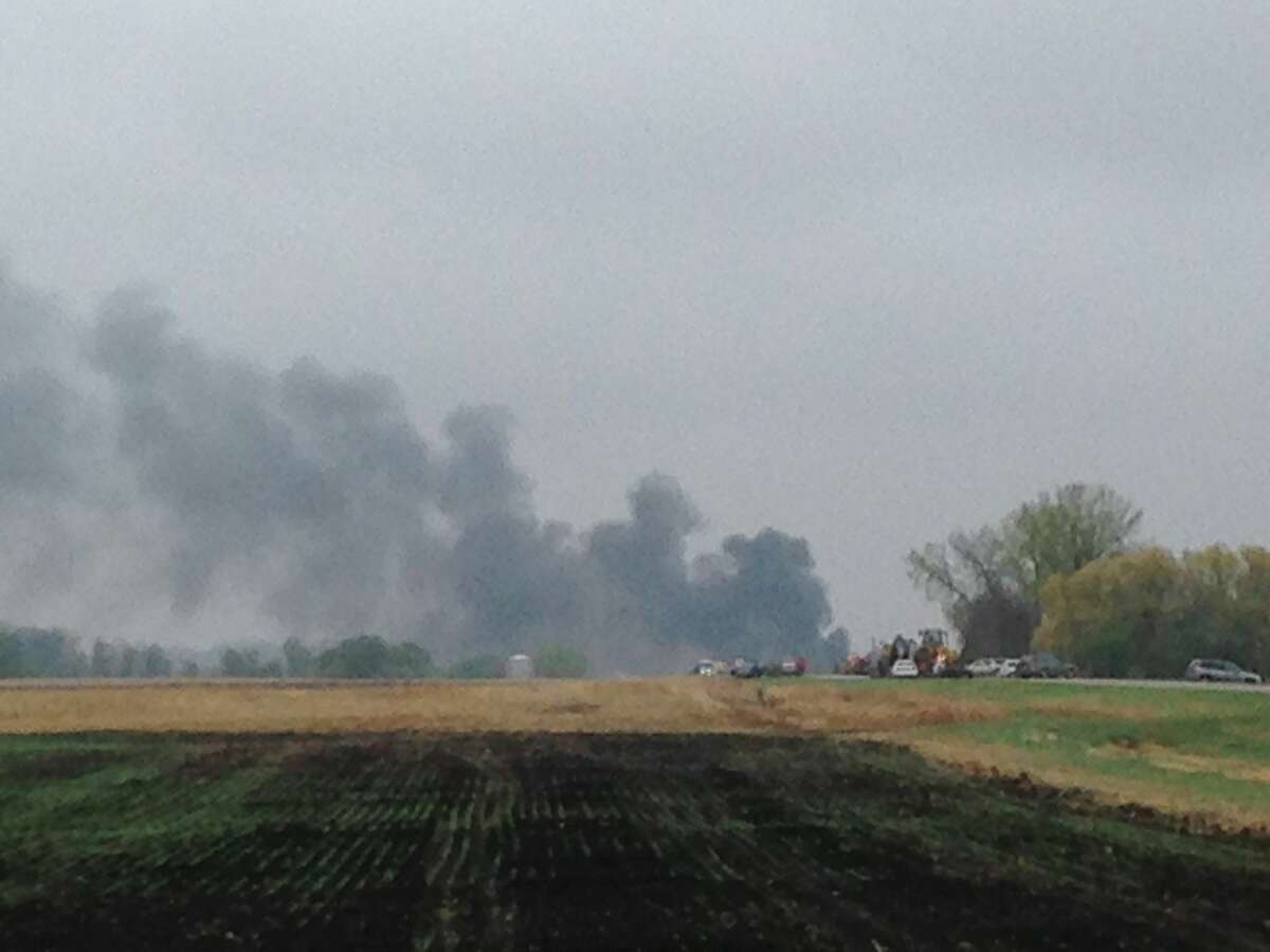 Smoke rises in the background past a field after BNSF Railway oil train derailed and caught fire in rural area about two miles from Heimdal, N.D. The central North Dakota town had to been evacuated due to the derailment and fire. (Tom Stromme/The Bismarck Tribune via AP)