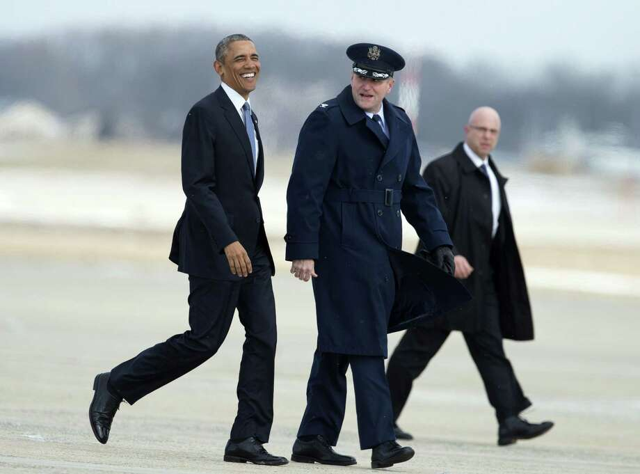 President Barack Obama, accompanied by 89th Airlift Wing Commander Col. John Millard, smiles as they walk on the tarmac at Andrews Air Force Base, Md., Wednesday, Jan. 7, 2015, as the president transferred from Marine One to Air Force One for a trip to Wayne, Mich.  The president will speak at the Ford Michigan Assembly Plant to highlight the workers in the resurgent American automotive and manufacturing sector. Walking on the back right is an unidentified Secret Service agent. Photo: (AP Photo/Manuel Balce Ceneta) / AP