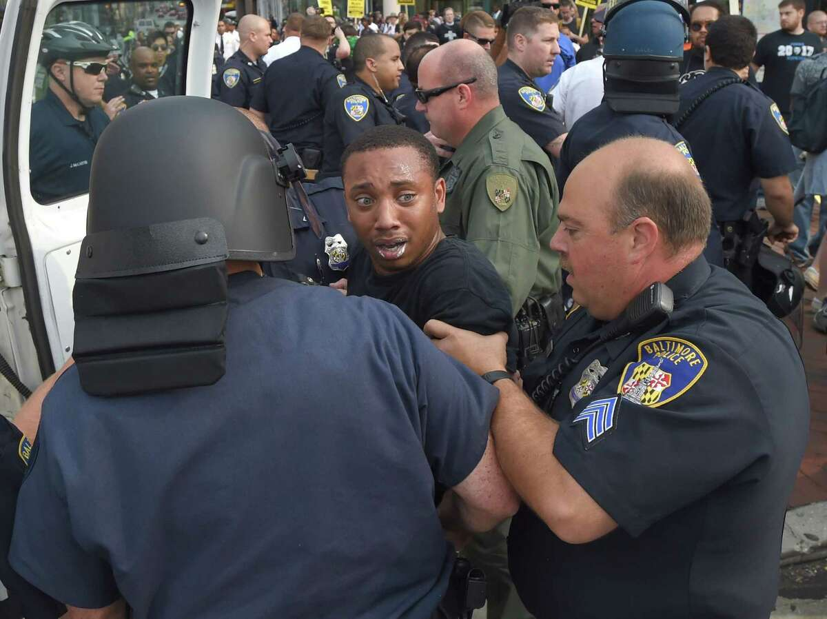 Kwame Rose is detained by police as protesters rallied outside the Baltimore courthouse during the first court hearing for six Baltimore police officers who are charged in the death of Freddie Gray, on Wednesday, Sept. 2, 2015 in Baltimore. A Baltimore judge refused to dismiss charges against the six police officers accused in the death in April of Gray, a black man who was in their custody. (Lloyd Fox/Baltimore Sun via AP) WASHINGTON EXAMINER OUT; MANDATORY CREDIT