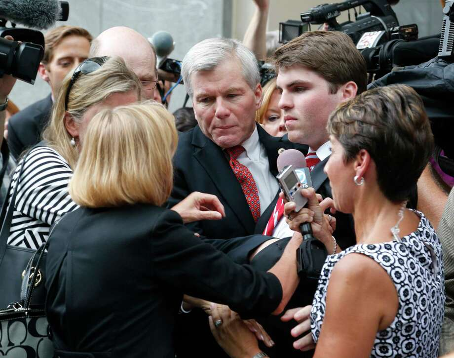 Former Virginia Gov. Bob McDonnell, center, is mobbed by media as he gets into a car with his son, Bobby, right,  after he and his wife, former first lady Maureen McDonnell, were convicted on multiple counts of corruption at Federal Court in Richmond, Va., Thursday. Photo: Steve Helber — The Associated Press  / AP
