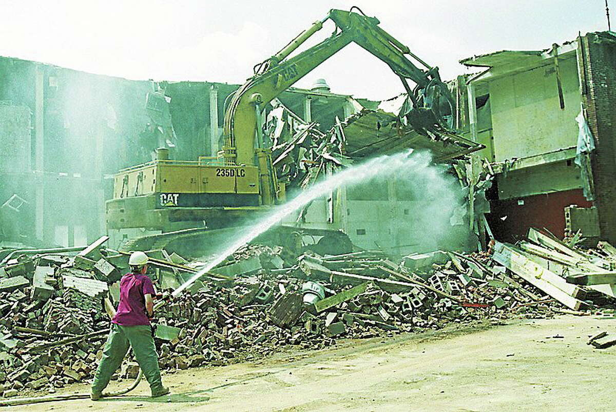 Peter Blonski of Standard Demolition Services uses a hose for dust control as a backhoe rips up the former Middletown Police Station on Church Street on May 3, 2001. (Photo by Irena Pastorello)