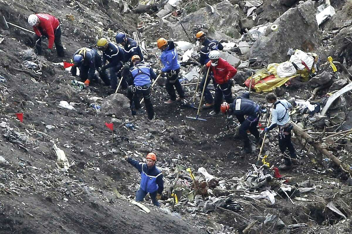 FILE - In this March 26, 2015 file photo, rescue workers work on debris of the Germanwings jet at the crash site near Seyne-les-Alpes, France. The co-pilot of Germanwings Flight 4525 tried a controlled descent on the previous flight that morning to Barcelona before the plane crashed into a mountainside in March on its way back to Germany, French air accident investigators said in a new report released Wednesday May, 6, 2015.
