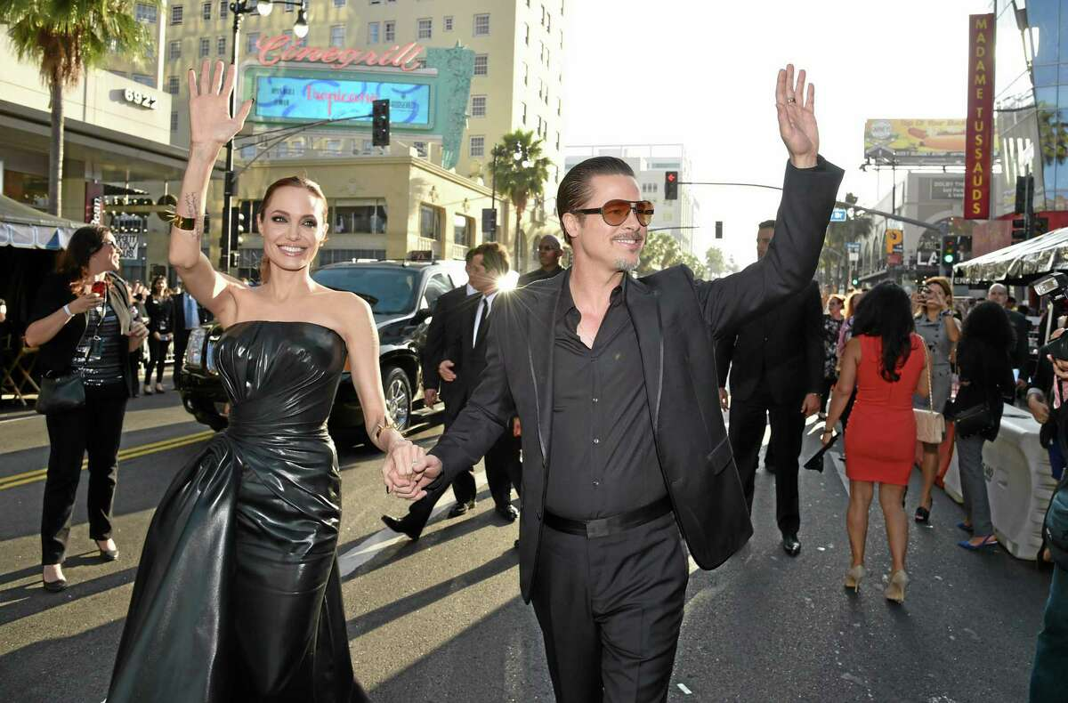 """Angelina Jolie, left, and Brad Pitt arrive at the world premiere of """"Maleficent"""" at the El Capitan Theatre on Wednesday, May 28, 2014, in Los Angeles."""