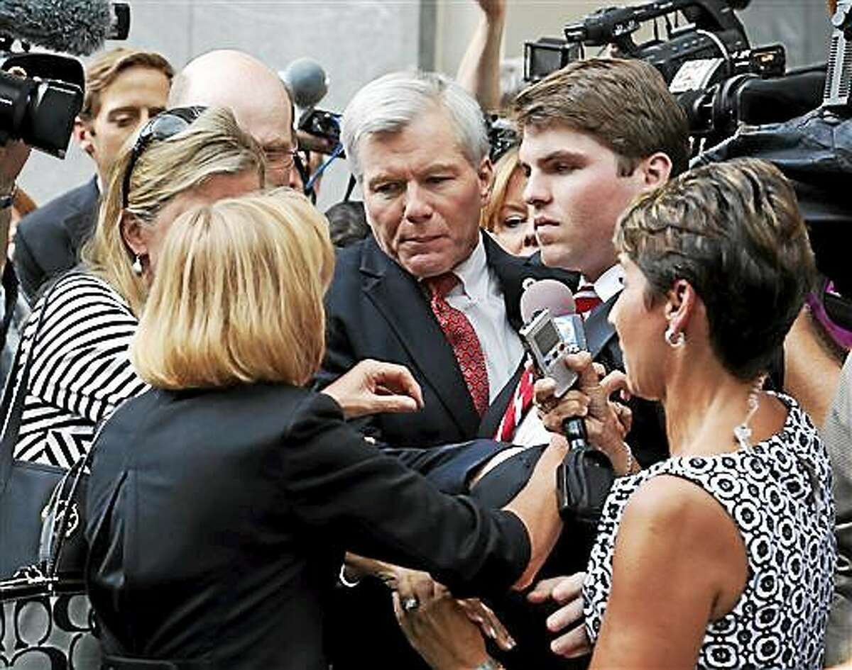 FILE - In this Thursday Sept. 4, 2014 file photo, former Virginia Gov. Bob McDonnell, center, is mobbed by media, friends and family as he gets into a car with his son, Bobby, right, after being convicted on multiple counts of corruption at Federal Court in Richmond, Va. The judge in the case will sentence McDonnell Tuesday, Jan. 6, 2015, and has received over 400 letters of support for the former governor. (AP Photo/Steve Helber, File)