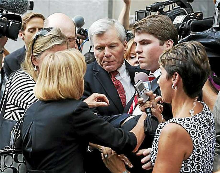 FILE - In this Thursday Sept. 4, 2014 file photo, former Virginia Gov. Bob McDonnell, center, is mobbed by media, friends and family as he gets into a car with his son, Bobby, right, after being convicted on multiple counts of corruption at Federal Court in Richmond, Va.  The judge in the case will sentence McDonnell Tuesday, Jan. 6, 2015, and has received over 400 letters of support for the former governor.   (AP Photo/Steve Helber, File) Photo: AP / AP/FILE