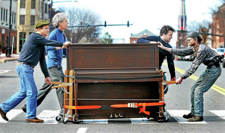 Michael Arafeh, owner of Coffeehouse Recording Studio in the North End of Middletown, in the cap on the far left, received an upright piano from the Buttonwood Tree in 2011. The only catch was he had to move it, along with a few helpers, across Main Street. Photo: File  / TheMiddletownPress