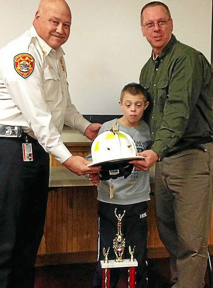 Middletown Fire Department Chief Robert Kronenberger joins Battalion Chief Ernie Cantwell and Cantwell's son, Benjamin. On display is a white leather fire helmet won by Cantwell, along with the title of biggest loser, in a department fitness challenge. Photo: Courtesy Middletown Fire Department