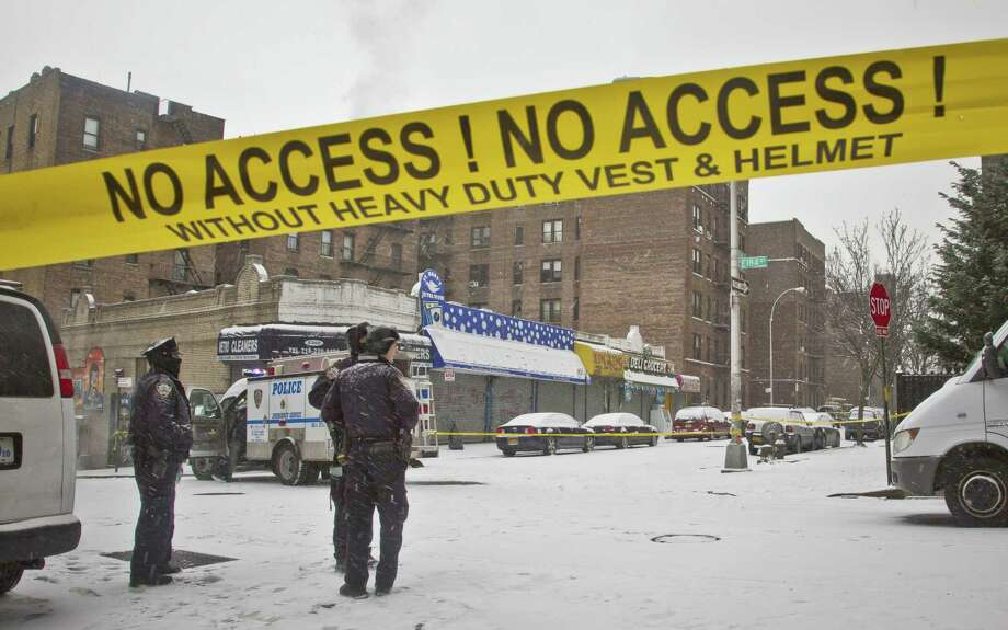 Police secure area with yellow tape where police and suspects exchanged gunfire, Tuesday, Jan. 6, 2015, in New York. A manhunt was under way Tuesday for at least two suspects who shot and wounded two New York City plainclothes police officers responding to a robbery Monday in the Bronx. Photo: (AP Photo/Bebeto Matthews) / AP