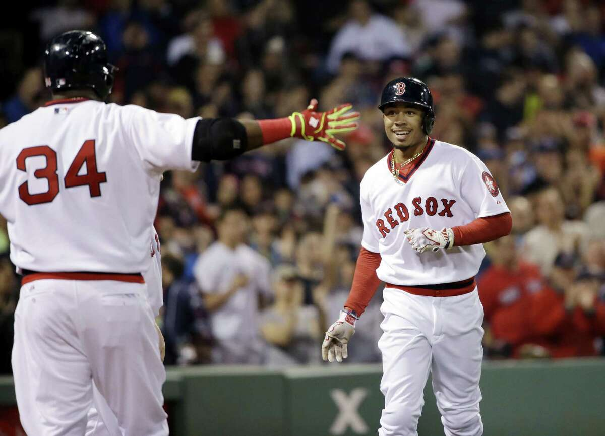 Boston Red Sox's Mookie Betts runs toward the dugout and celebration with designated hitter David Ortiz (34) after he hit a solo homer against the Tampa Bay Rays in the eighth inning of a baseball game at Fenway Park in Boston, Tuesday, May 5, 2015. It was Betts' second home run of the game. The Red Sox won 2-0. (AP Photo/Elise Amendola)