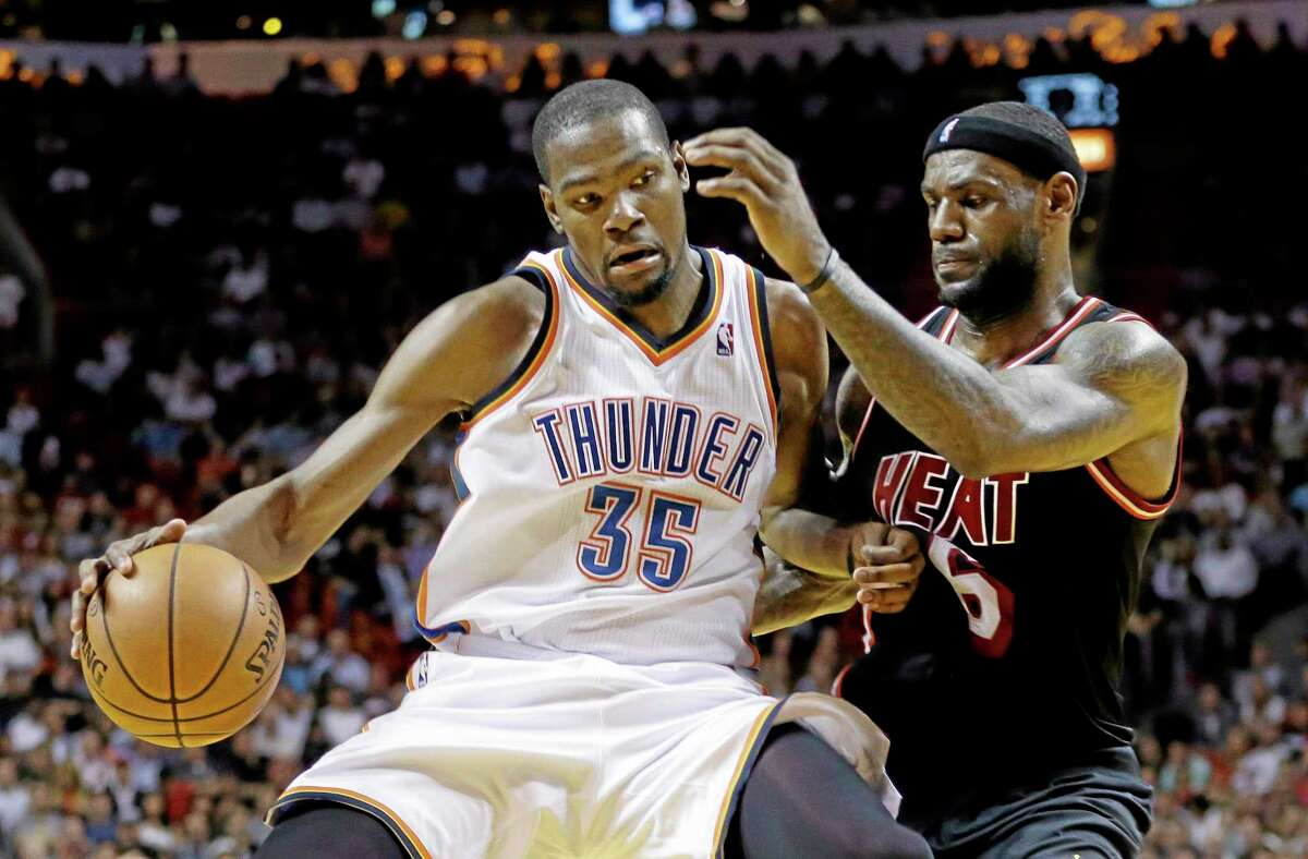 In this Jan. 29 file photo, Miami Heat star LeBron James, right, defends Oklahoma City Thunder star Kevin Durant.