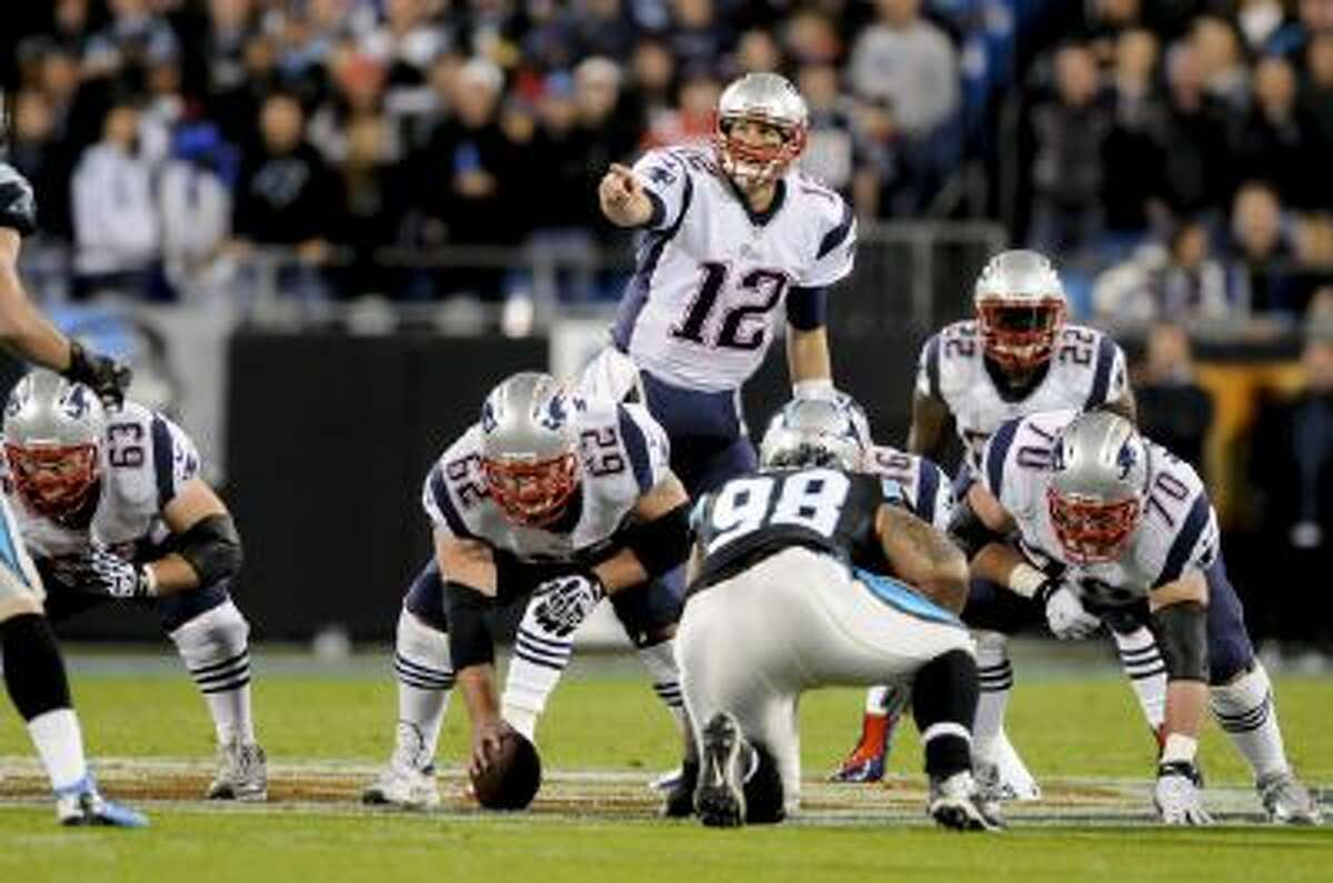 New England Patriots quarterback Tom Brady (12) gives directions at the line of scrimmage during an NFL football game against the Carolina Panthers in Charlotte, NC, Monday, Nov. 18, 2013.