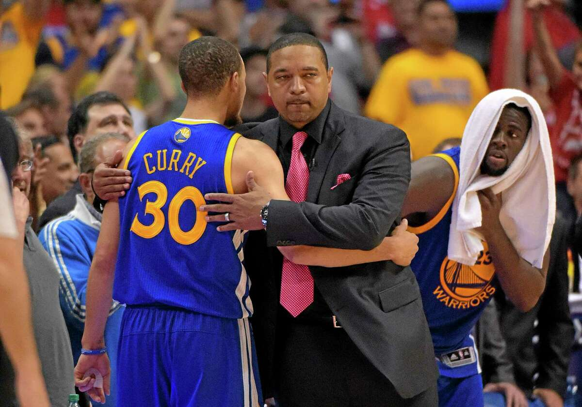 Golden State Warriors head coach Mark Jackson, center, hugs guard Stephen Curry after Curry was taken out of the game during the second half of a Game 7 loss to the Los Angeles Clippers on Saturday. Jackson was fired on Tuesday.