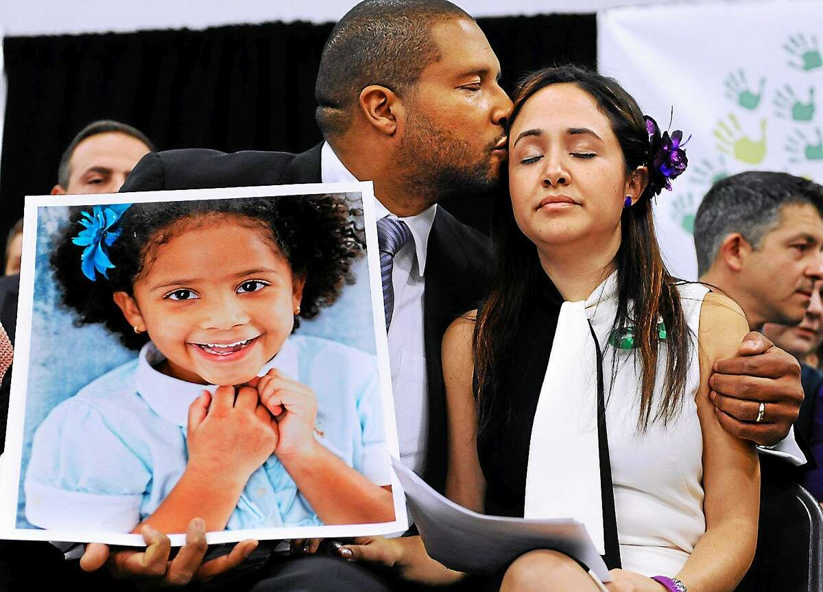 Jimmy Greene, left, kisses his wife Nelba Marquez-Greene as he holds a portrait of their daughter, Sandy Hook School shooting victim Ana Marquez-Greene, at a news conference in Newtown, Conn., on Jan. 14, 2013.