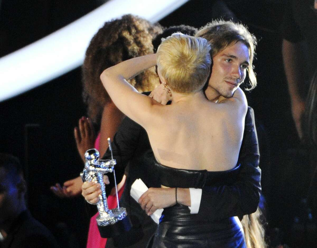 FILE - In this Aug. 24, 2014 file photo, Miley Cyrus embraces Jesse Helt at the MTV Video Music Awards at The Forum in Inglewood, Calif. Helt, a homeless man, accompanied Cyrus to the MTV Video Music Awards and accepted her award for video of the year.