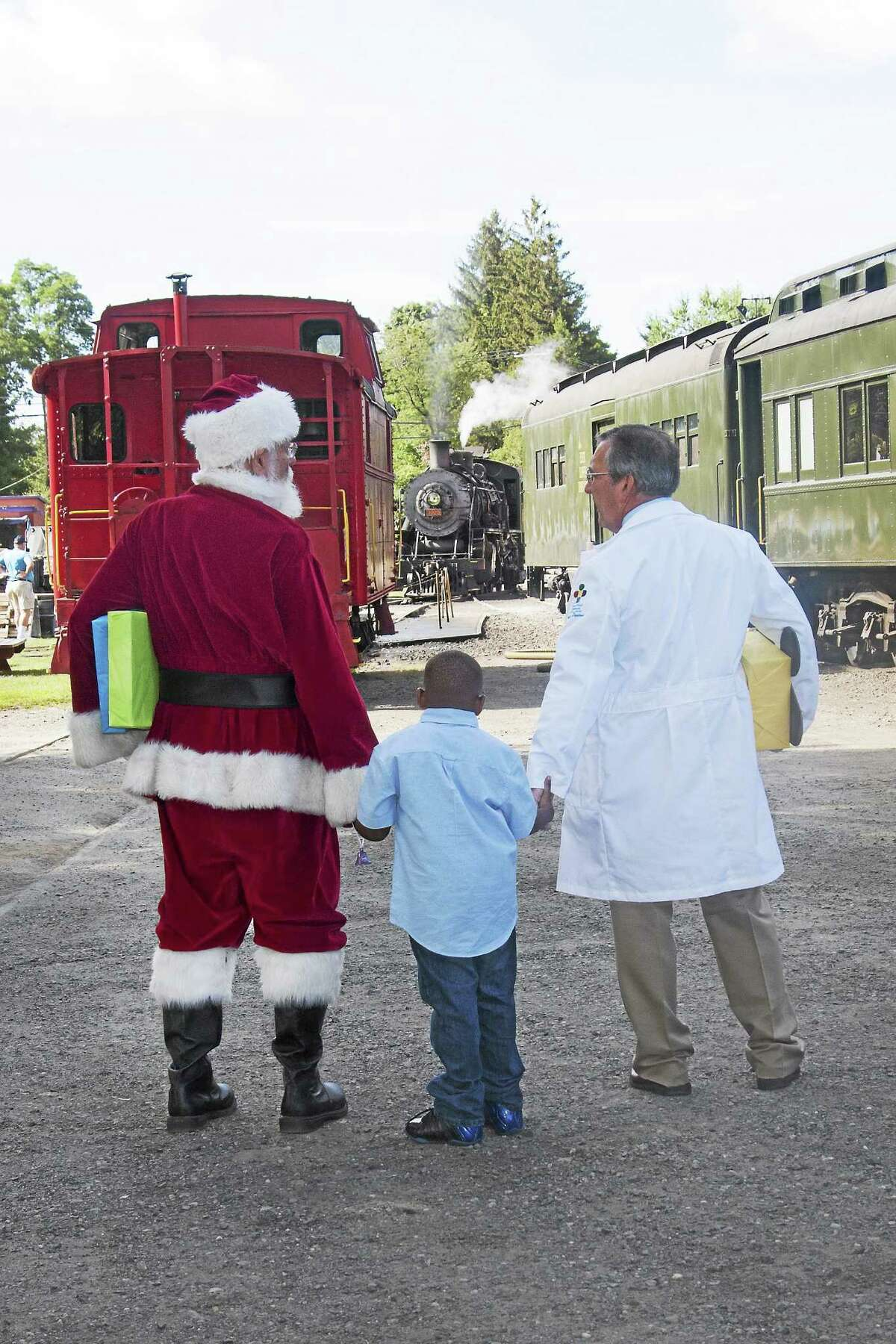 Photos courtesy of CCM/Essex Steam Train Santa, a young patient and a medical practitioner from Connecticut Children's Medical Center.