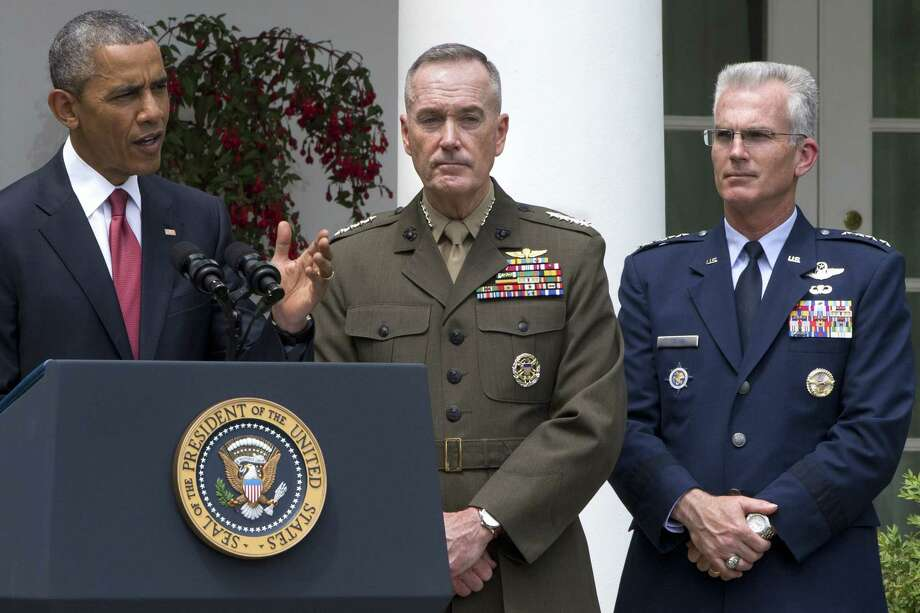Marine Gen. Joseph Dunford Jr., center, with Air Force Gen. Paul Selva, listens as President Barack Obama announces that he will nominate Dunford as the next chairman of the Joint Chiefs of Staff, and Selva as the vice chairman on May 5, 2015 in the Rose Garden of the White House in Washington. Photo: AP Photo/Jacquelyn Martin  / AP