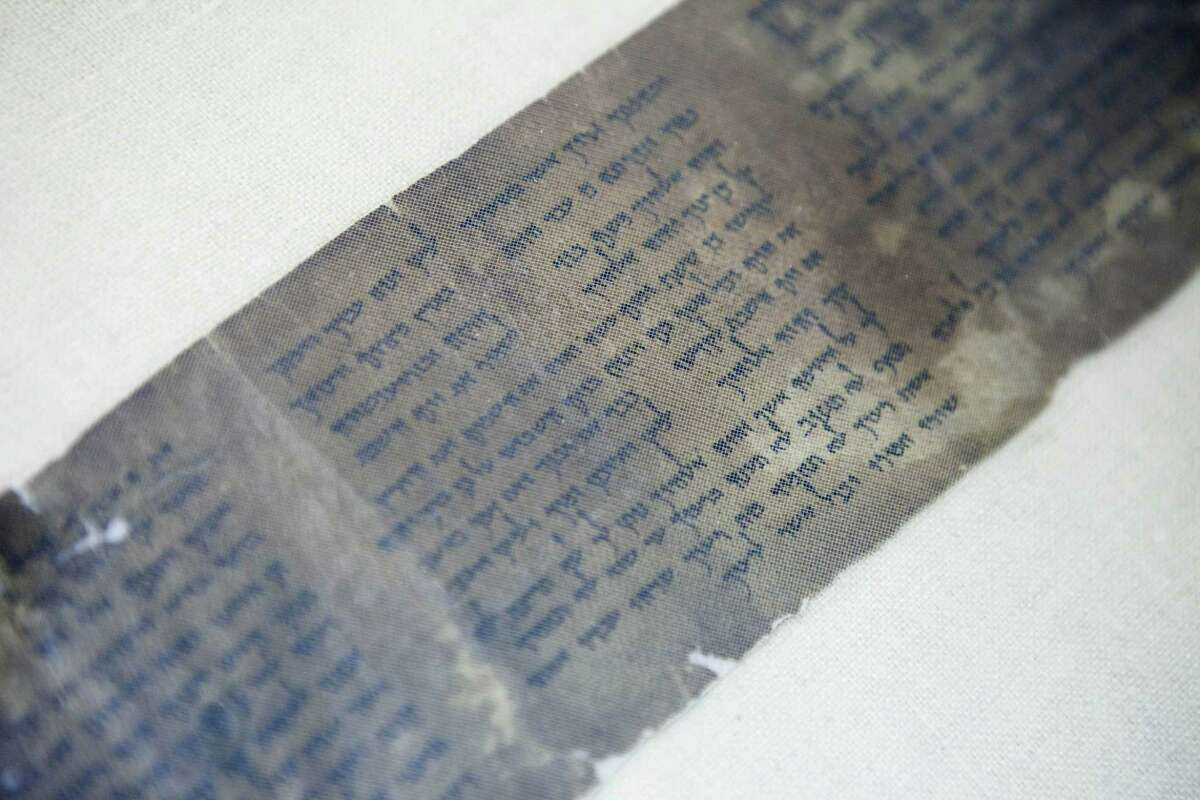 FILE - This Friday, May 10, 2013 file photo shows the world's oldest complete copy of the Ten Commandments, written on one of the Dead Sea Scrolls in Jerusalem. The manuscript is on rare display at Israel's national museum in an exhibit of objects from pivotal moments in the history of civilization.