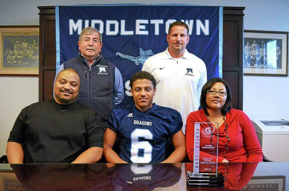 John Berry — The Middletown Press Middletown High School football star Dario Highsmith Jr., center, was named the Gatorade player of the year for Connecticut. Seated with him are his parents Dario Highsmith Sr and Monica Highsmith. Behind them are Middletown High School's athletic director Mike Pitruzzello and head football coach Sal Morello. Photo: Journal Register Co.