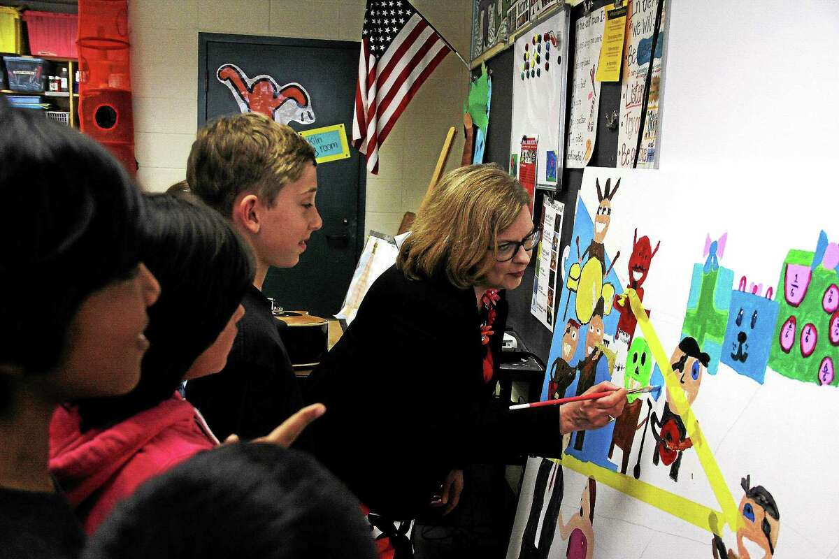 Dianna Wentzell, Commissioner of the State Department of Education, paints a mural with students Tuesday at Lyman elementary, a Higher Order Learning School.