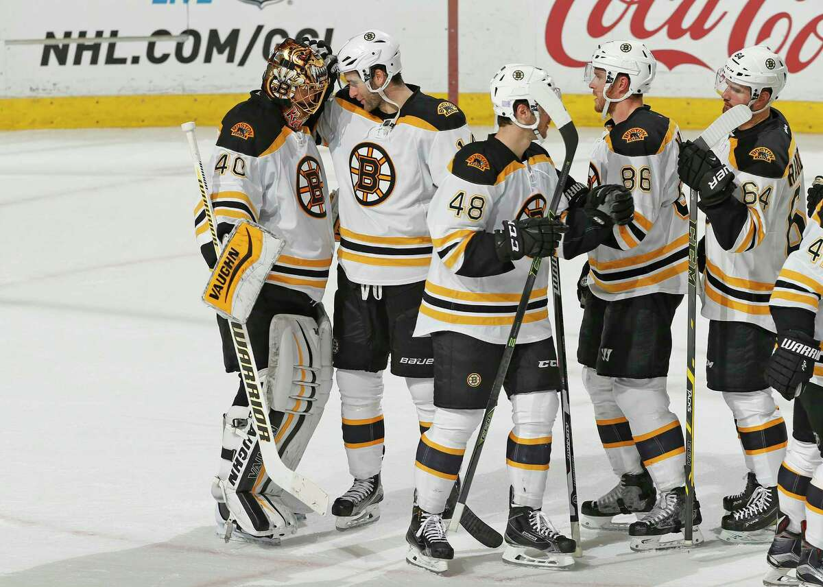 Boston Bruins goaltender Tuukka Rask (40) is congratulated by teammates following Friday's game against the Florida Panthers in Sunrise, Fla.