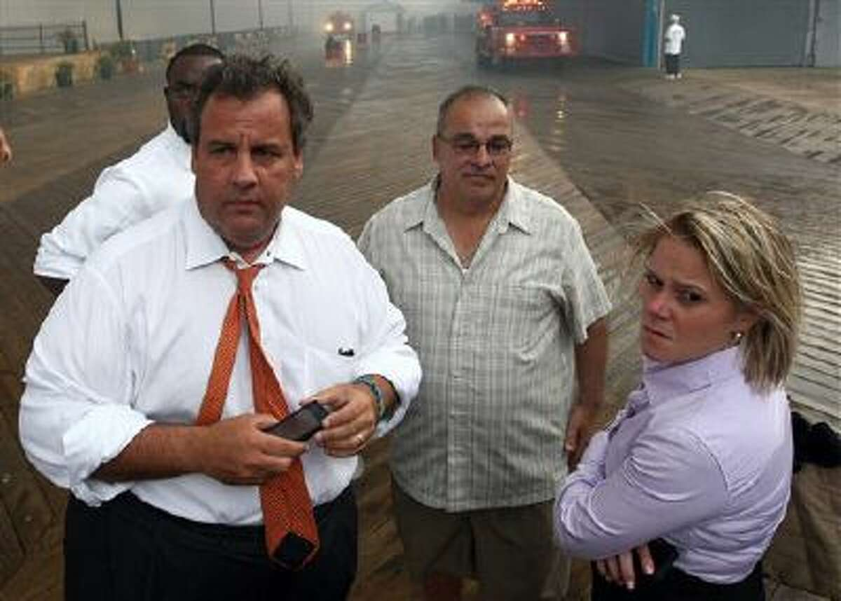 """Deputy Chief of Staff Bridget Anne Kelly, right, stands with New Jersey Gov. Chris Christie, left, Sept. 12 during a tour of the Seaside Heights, N.J., boardwalk after it was hit by a massive fire. Christie fired Kelly on Thursday and apologized for his staff's """"stupid"""" behavior, insisting that he had no idea anyone around him had engineered traffic jams as part of a political vendetta against a Democratic mayor."""