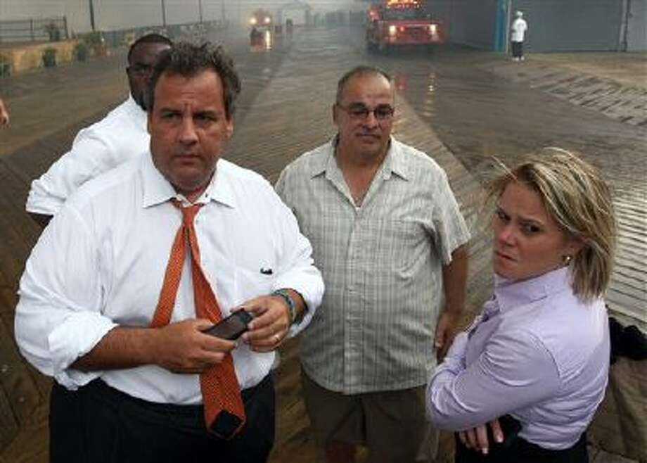 """Deputy Chief of Staff Bridget Anne Kelly, right, stands with New Jersey Gov. Chris Christie, left, Sept. 12 during a tour of the Seaside Heights, N.J., boardwalk after it was hit by a massive fire. Christie fired Kelly on Thursday and apologized for his staff's """"stupid"""" behavior, insisting that he had no idea anyone around him had engineered traffic jams as part of a political vendetta against a Democratic mayor. Photo: AP / Office of the Governor"""