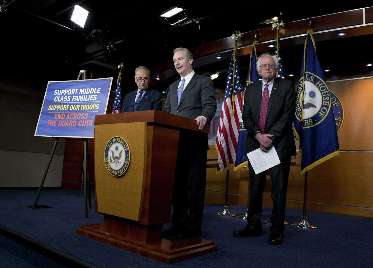 Rep. Chris Van Hollen, D-Md.,, center, flanked by Sen. Bernie Sanders, I-Vt., right, and Sen. Charles Schumer, D-N.Y., speaks during a news conference on Capitol Hill in Washington Wednesday against the Republican backed budget that they say will hurt American middle class families.
